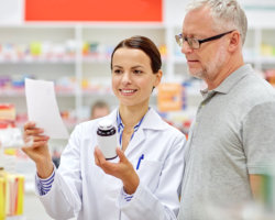 pharmacist and old woman looking at the prescription